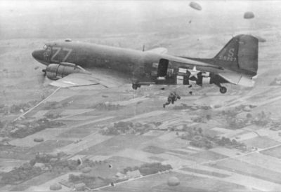 Springende_Amerikaanse_parachutisten_vanuit_een_Dacota_boven_Groesbeek_17_september_1944.-1